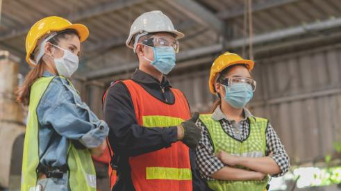 Group of three construction workers wearing masks