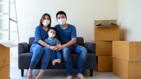 Family with masks and moving boxes