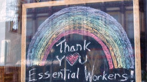 A chalkboard sign saying 'Thank you essential workers' hanging in a window