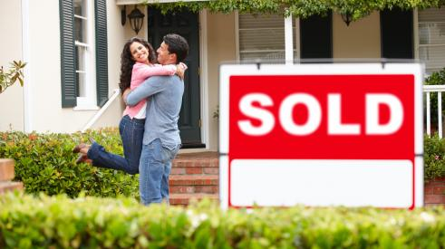 Smiling couple with sold house