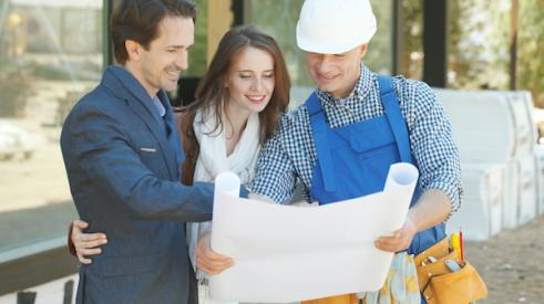 Builder smiling and showing plans to smiling clients