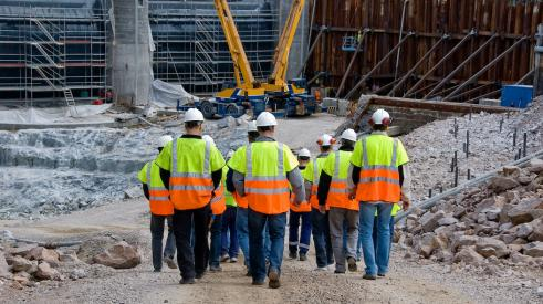 Group of construction workers walking to building site