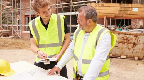 Home builder talking to apprentice
