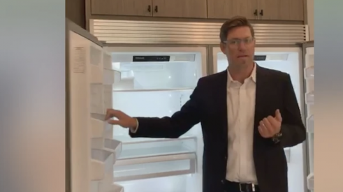 Thomas James Homes CEO Thomas Beadel shows off 6-foot freezer/fridge combo during Facebook open house tour.