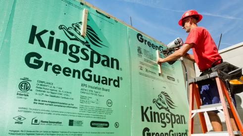 Construction crew installing Kingspan GreenGuard building wrap on home exterior