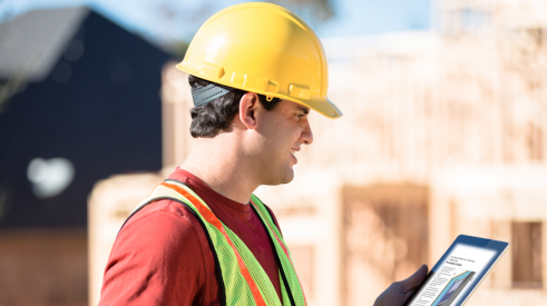Construction worker wearing hard hat and looking at tablet with specifications on building jobsite