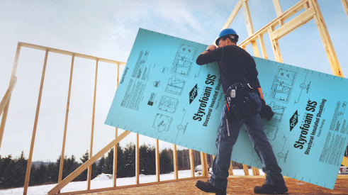 Man carrying sheathing panel for home walls