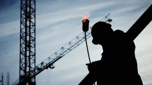 Construction worker alone on jobsite with towering cranes