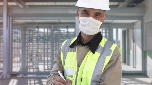 Happy construction worker on jobsite wearing protective facemask