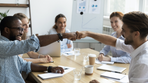 Coworkers fist bumping at a conference table show teamwork and positive company culture