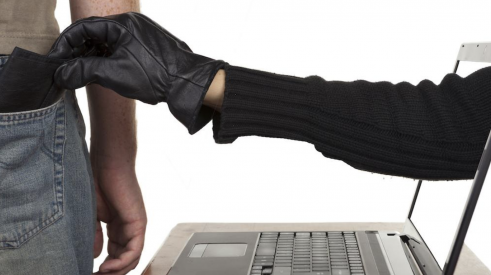 Hand of cyber criminal reaching out from laptop screen to pick-pocket