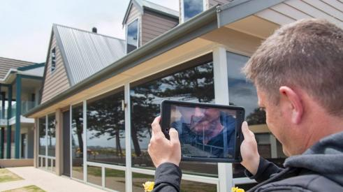 Home builder using a tablet for a virtual inspection