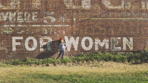 "Little girl in front of brick wall that says ""for women"""