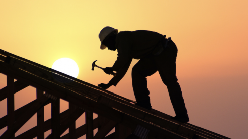 Man using hammer building home roof at dawn