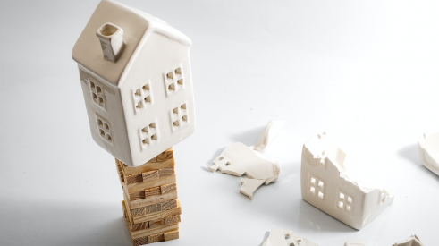 Model house teetering on Jenga blocks as an example of home builder possible success or failure