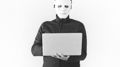 Person in mask using laptop
