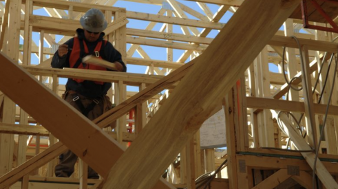 worker checks timber framing for house under construction