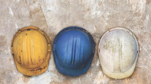 yellow, blue, and white construction hard hats in a row