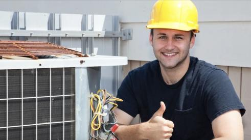 Young construction worker working on HVAC and giving a thumbs-up.