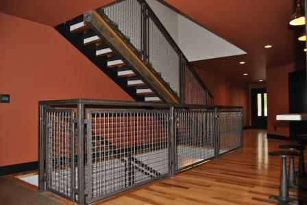 The woven wire mesh of this stair railing was fabricated into panels and installed on site to fit with the home's rustic-modern aesthetic.