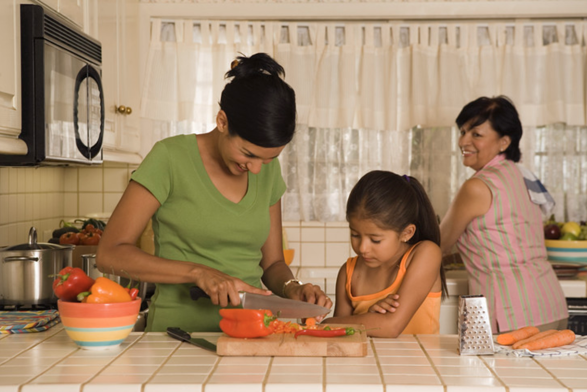 three generations of women chopping vegetables in the kitchen