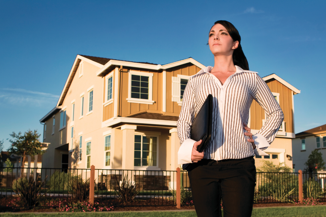 Successful home salesperson standing in front of a new home
