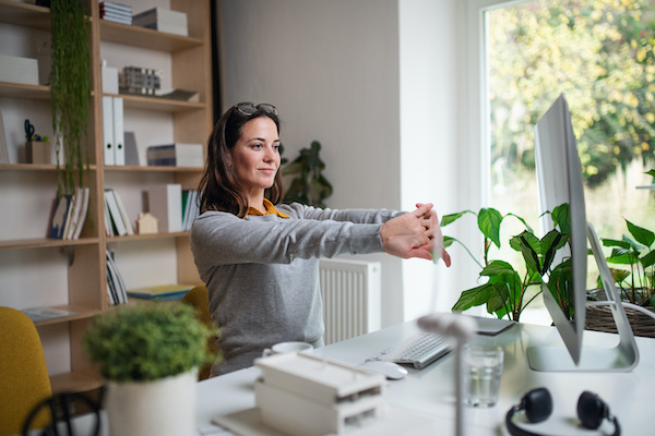 woman sitting at desk stretching shoulders as she works from home